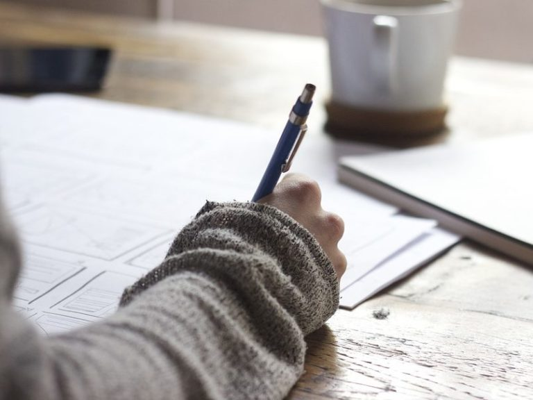 a person's hand is holding a pencil, papers are in front of them