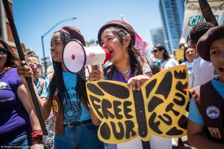 "Photo of two Radical Monarch troop members, holding a butterfly sign that reads ""Free Our Future"""