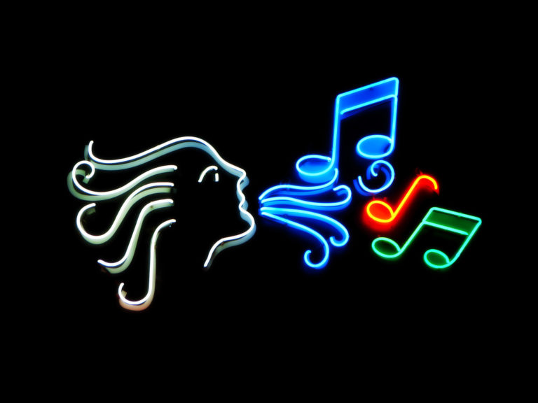 Neon illustration of a face breathing out music notes