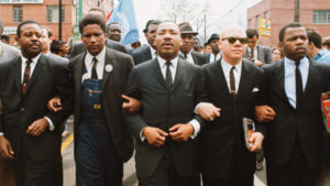 Dr. Martin Luther King Jr. walking arm in arm during a march