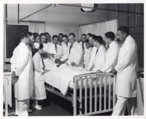 A historical photo of doctors and medical staff surrounding a patient