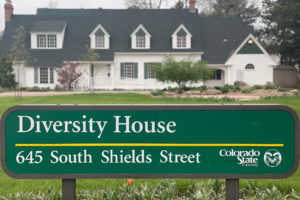 The Diversity House front lawn sign, with the white Diversity House standing behind