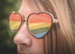 Close up of a person wearing heart-shaped rainbow sunglasses