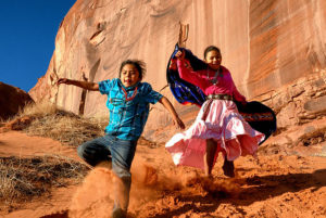 Two indigenous children playing on red rocks